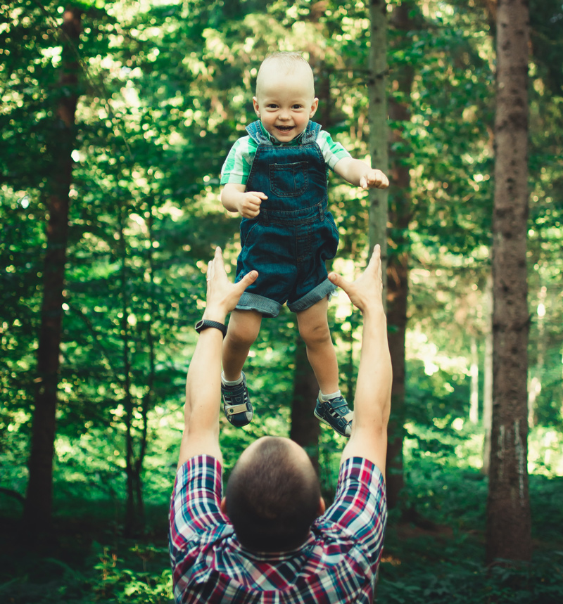 A dad playing with his toddler throwing him in the air