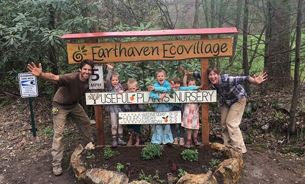 Earthaven kids celebrating planting native flowers by the Earthaven Ecovillage sign