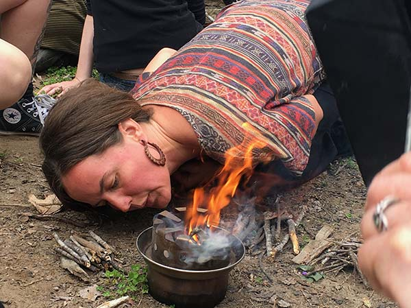 Kelly Gaskill making a cooking fire at the Reaching Nature Connection Conference