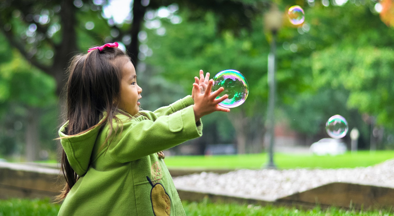 Little girl catching blown bubbles in the park