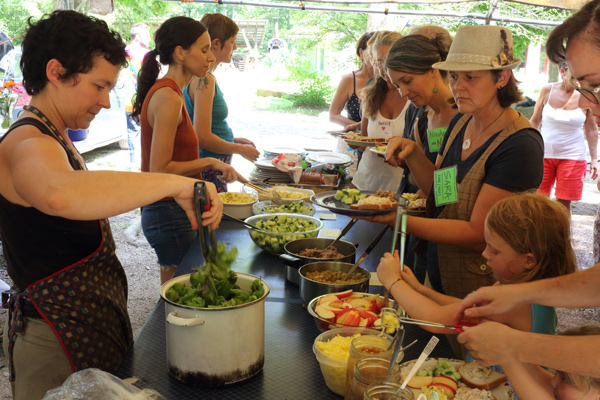 Lunch break at a SOIL class with students lined up at buffet of fresh natural foods