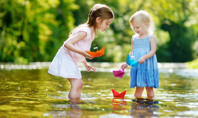 Two girls playing in a stream with origami boats